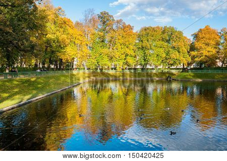 ST PETERSBURG RUSSIA-OCTOBER 3 2016. Autumn landscape Karpin pond in Summer garden with walking people. Autumn landscape of St Petersburg Russia. Autumn park with yellow autumn leaves near the pond