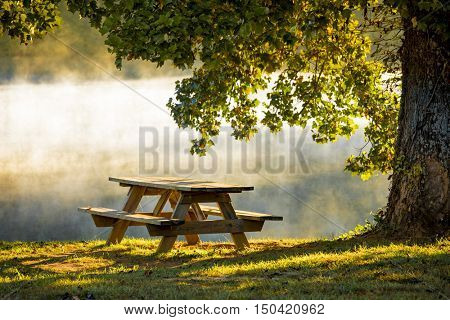 Picnic table in morning light with mist