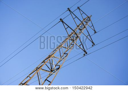 Old and rusty high power grid pylon against blue sky