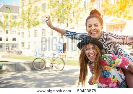 Laughing young female friends piggy back riding outdoors on a residential urban street posing with outstretched arms like an airplane with copy space and sun glow