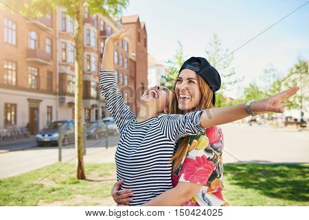 Laughing frivolous young women posing together in a close embrace laughing and joking with outstretched arms