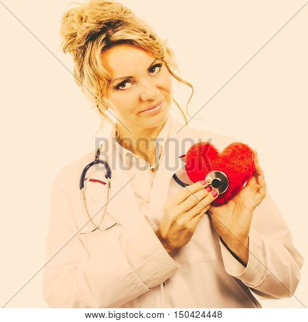 Doctor With Stethoscope Examining Red Heart.