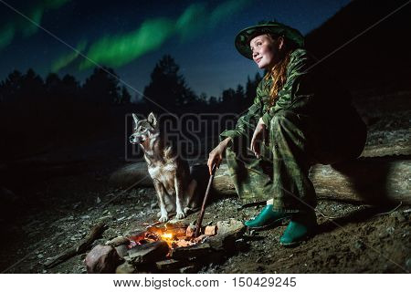 Scout girl with her dog around campfire at night with stars and polar lights.
