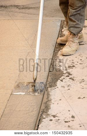 A concrete finisher using a walking edger tool on wet concrete.