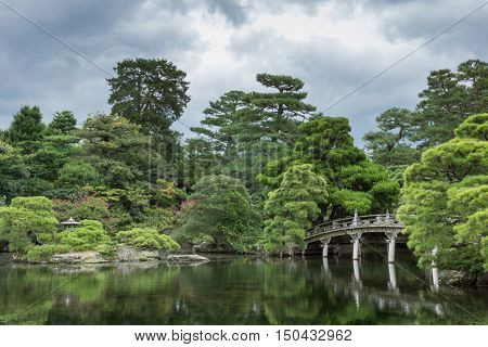 Kyoto Japan - September 14 2016: Part of the Japanese garden at the imperial palace showing bridge pond trees and flowers under heavy sky.