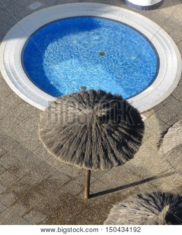 a hotel swimming pool with straw umbrella