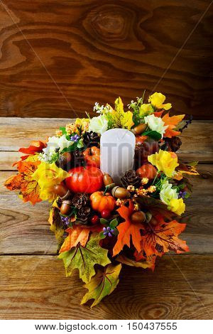 Thanksgiving centerpiece with candle and artificial fall leaves vertical. Thanksgiving greeting with fall decor. Fall decoration.