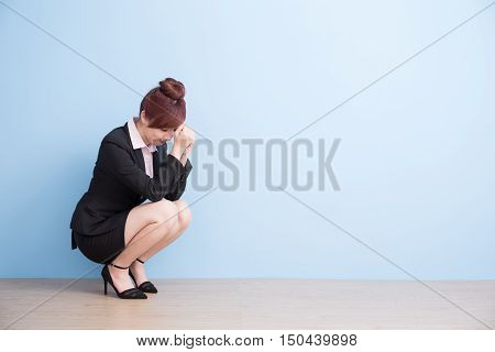 business woman is painful and unhappt on the floor with blue background asian