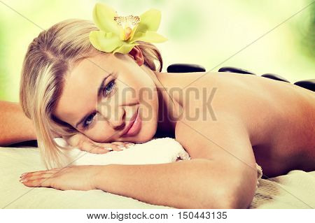 Stone massage sensual woman getting a hot stone massage at spa salon. Instagram filter
