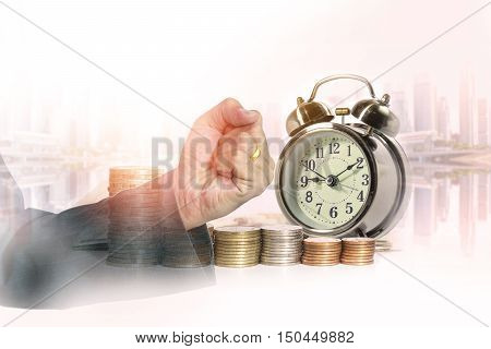 Double exposure of hand of business fist with a row of stack money coins and analog clock on the blurred cityscape background concept for business finances and saving money.