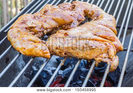 Pork roast with crackling roasting on charcoal grill.