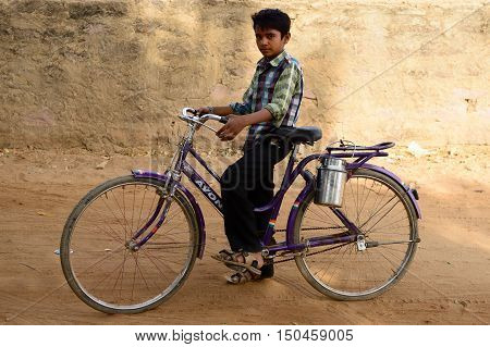 BHUJ RAN OF KUCH INDIA - JANUARY 13: The young boy is cycling for the milk to the nearby shop in the village on the desert in of Ran of Kuch in the Gujarat state in India Ran of Kuch in January 13 2015