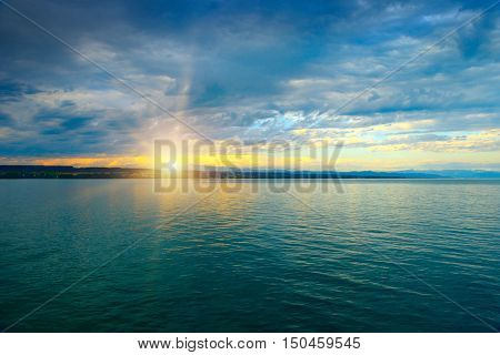 Dawn above sea and blue sky with white clouds.