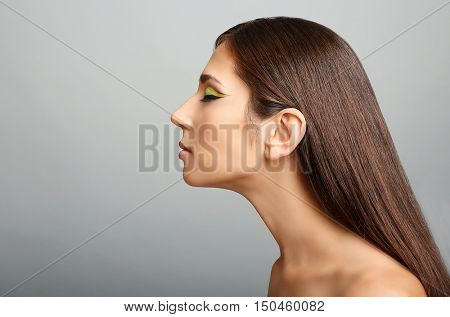 Portrait of young beautiful woman with colourful eye makeup on grey background