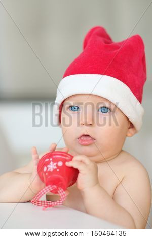Baby boy with blue eyes christmas portrait in Santa Claus hat