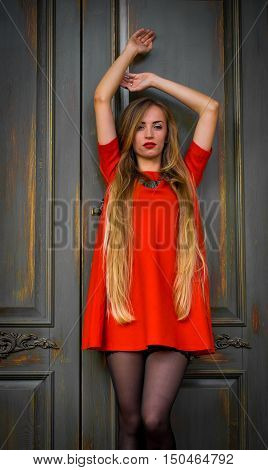Fashionable young girl with red lips and a red dress with long hair on retro background door.