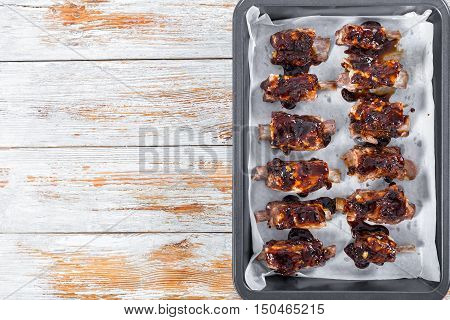 delicious ribs seasoned with spicy basting sauce prepared for grill in oven-tray on white peeling paint planks copy space left view from above