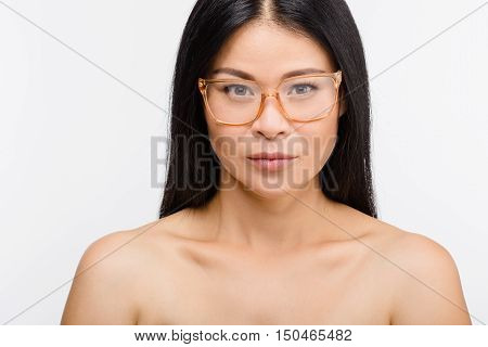 Image of beautiful Korean woman in glasses isolated over white background in studio. Brunette lady posing for photographer.