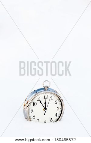Metallic old clock in snow copy space. New year greeting card christmas concept.