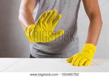 Young man in a yellow rubber gloves refuses to do housework, snowing 'no' sighn