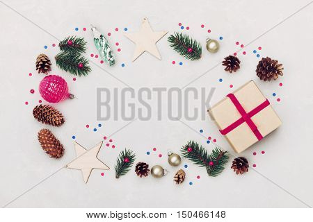 Christmas background of gift box, fir tree, conifer cone and holiday decorations on white table top view. Flat lay styling.