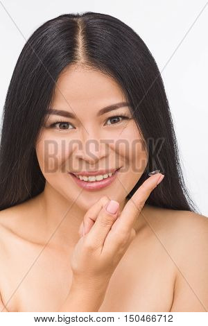 Picture of happy smiling Korean or Asian woman or lady looking at camera and holding contact lenses isolated on white.