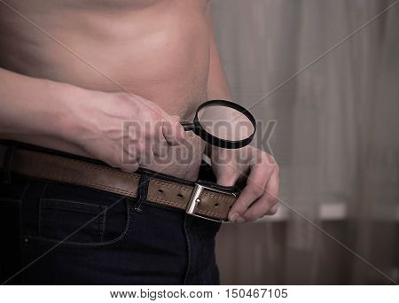 Guy having size worries and checking out with a magnifying glass. Health and impotence