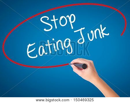 Women Hand Writing Stop Eating Junk With Black Marker On Visual Screen.