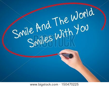 Women Hand Writing Smile And The World Smiles To You With Black Marker On Visual Screen