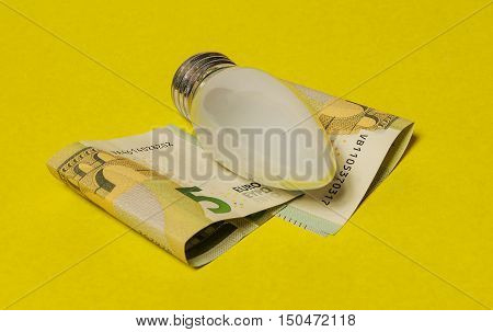 On a yellow background are five euro banknotes and electric incandescent lamp