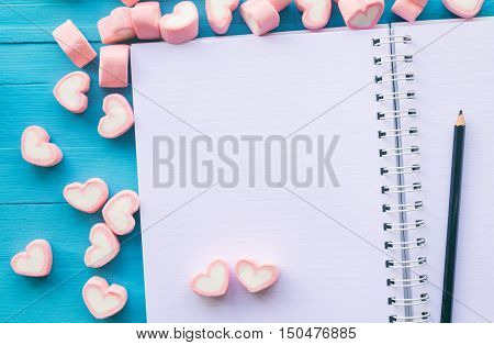 Pink heart shape marshmallow on the notebook for love theme and Valentine concept. You can apply for love background, love wallpaper, day of love and everything about love for your design.