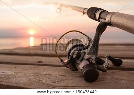 Fishing reel and rod lying on wooden pier over the sunset lake. Sun over horizon