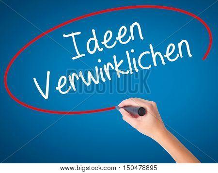 Women Hand Writing Ideen Verwirklichen ( Realize Ideas In German) With Black Marker On Visual Screen