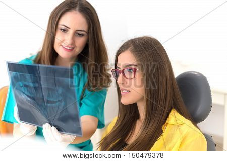 Female dentist showing her patient x-ray radiography, in the Dental Clinc