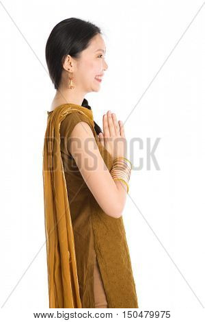 Side view young mixed race Indian Chinese girl in traditional punjabi dress greeting, standing isolated on white background.