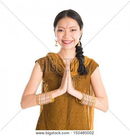 Young mixed race Indian Chinese girl in traditional punjabi dress showing greeting gesture, standing isolated on white background.