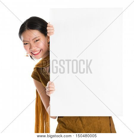 Portrait of young mixed race Indian Chinese girl in traditional punjabi dress hiding behind a blank white paper card, standing isolated on white background.