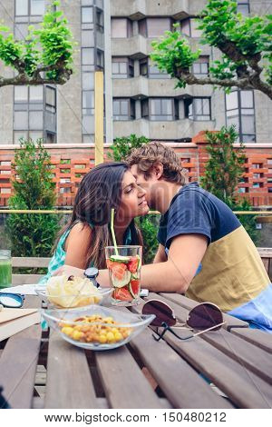 Young man whispering to beautiful woman sitting around of table with healthy drinks and snacks in a summer day outdoors