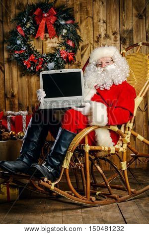 Modern Santa Claus at his wooden house surfing in the Internet with his laptop. Christmas. Copy space.