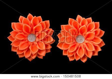 Handmade orange bows of satin ribbon and rhinestones.