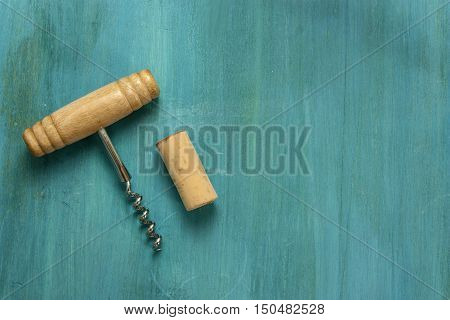 A photo of an old-fashioned corkscrew with a cork, shot from above on a vibrant blue background texture with plenty of copyspace. A design template for a wine list or a tasting invitation