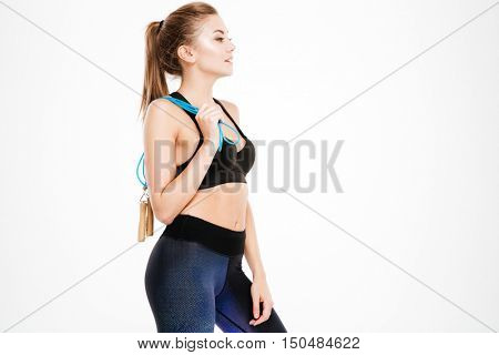 Side view portrait of a beautiful woman in sports wear standing with skipping rope isolated on a white background