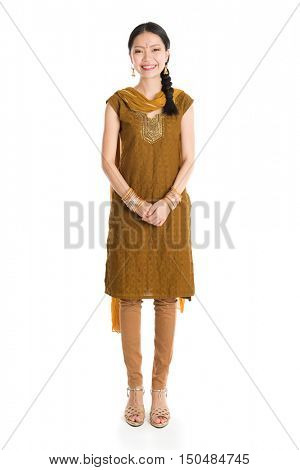 Portrait of young mixed race Indian Chinese woman in traditional punjabi dress smiling and looking at camera, full length standing isolated on white background.