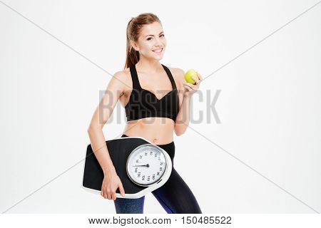 Happy cheerful fitness woman holding weight scales and green apple isolated on a white background
