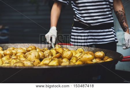 Country fair, vendor mix dish. Roasted potatoes cooked outdoors in big metal cauldron pot. Cookout vegetable meals. Fresh organic snack, potatoes cooked on grill flame. Street food, fast food.