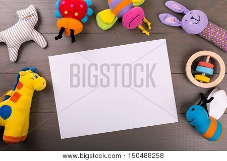 stuffed baby toys on wooden background with blank paper sheet
