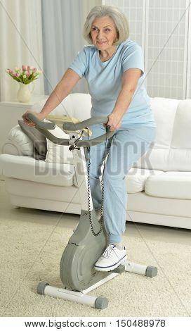 Happy senior woman exercising on a bike