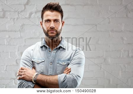 Portrait of young goodlooking man against white brickwall. Lots of copyspace.