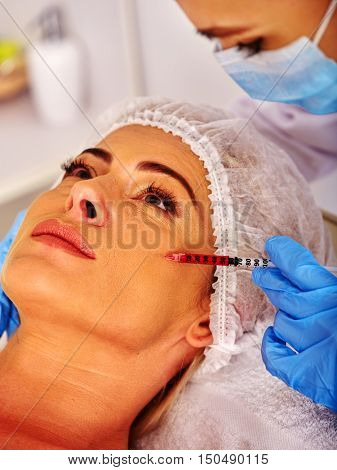 Woman middle-aged in spa salon with mesotherapy beautician. Beauty woman giving Mesotherapy Face injections .