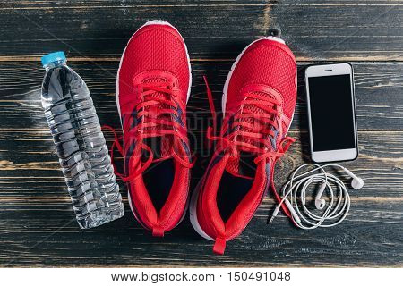 Fitness concept Essential running item Overhead view of running shoe water smartphone and earphone